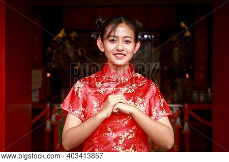 Asian Girl Wearing A Red Cheongsam Dress Standing Smiling In The Shrine Raise Your Hand To Bless Eve