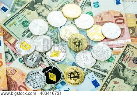 Various Cryptocurrency Coins On Paper Dollars And Euros. Bitcoin, Ethereum, Litecoin And Others Mode