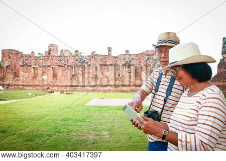 Asian Couples, Elderly Travelers Hold Tab To View Historical Data In Ayutthaya, Thailand