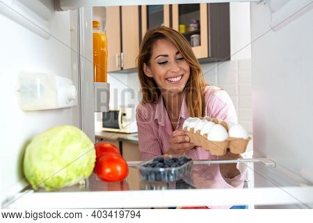 Happy Young Woman ,observed From The Fridge Perspective, Holding A Pack Of Eggs