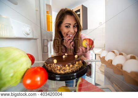 Pretty Young Woman Having Food Related Doubts, Will It Be An Apple Or A Cake
