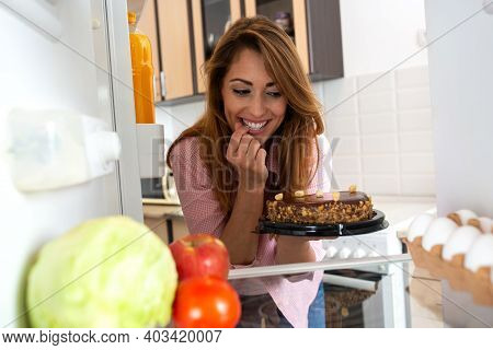 Young Woman Hypnotized By Magnificent Piece Of Tasty Brown Chocolate Cake