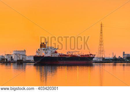 Commercial Cargo Ship At Port Adelaide Docks Viwed Across Port River At Sunset