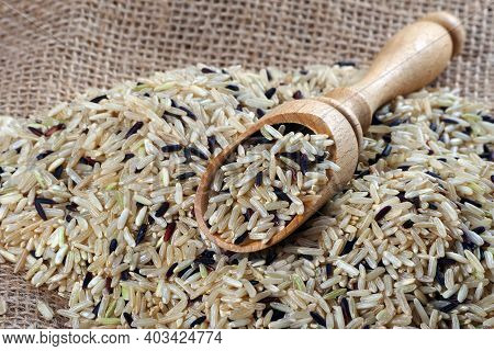 Rice In A Wooden Scoop Close-up. Wild Brown Rice
