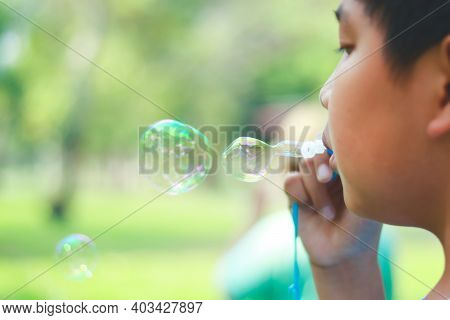 An Asian Boy Is Playing Blowing Bubbles. At The Park