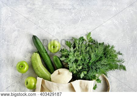 Various Fresh Vegetables And Fruits, Greenery In A Reusable Shopping Cotton Bag On A Concrete Gray B
