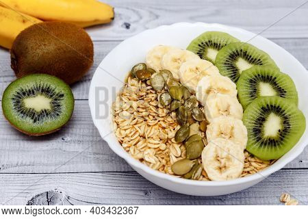Bowl Of Oatmeal Porridge With Banana, Kiwi And Pumpkin Seeds. Healthy Food For Breakfast.