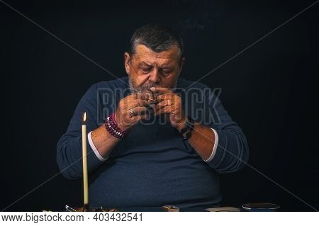 Nice Low Key Portrait Of Senior Man - Soothsayer Lighting Up A Cigar