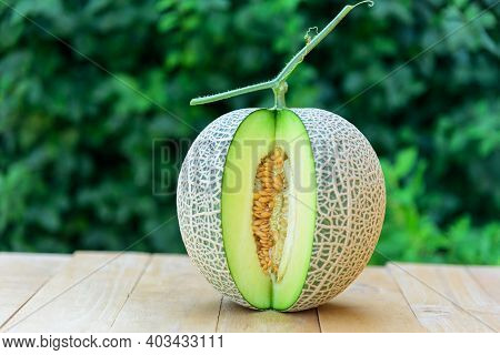 A Piece Of Fresh Green Melon On Wood Plate