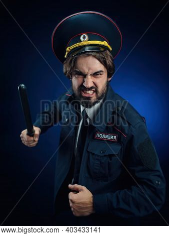 A Man In A Russian Police Uniform With A Baton. English Translation Of Police