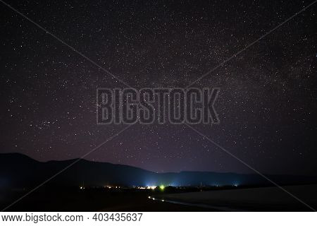 Night Sky With Lot Of Shiny Stars And Countryside With Houses