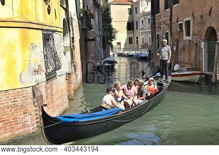Venice, Italy - 3 August, 2016: Tourists Enjoying The Gondolas In A Canal. The Gondolas Are The Most