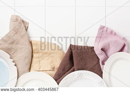 Four Multi-colored Linen Napkins And Four Empty White Plate On Cooking Stone Table With Kitchen Towe