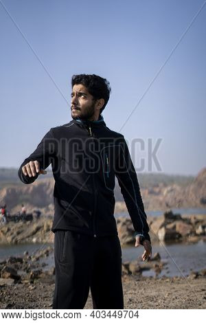 Young Indian Fit Boy Getting Ready For His Workout Routine By Wearing His Tracksuit.