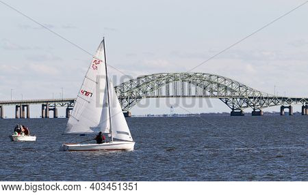Babylon, New York, Usa - 7 December 2019: Sailboat Sailing With The Great South Bay Bridge In The Ba