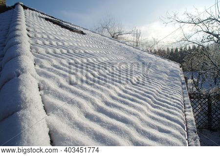 Snow On The Roof Tiles In The Sun Beam. White Winter Season.