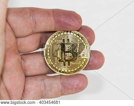 A Hand Is Holding A Gold Bitcoin Coin In Its Fingers With A White Backgound For Copy Space.