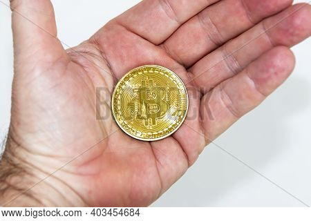 Gold Bitcoin Coin In The Palm Of A Hand With A White Background.