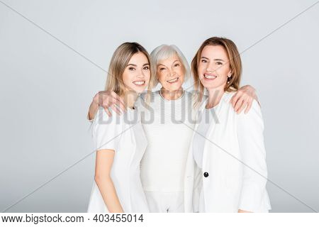 Three Generation Of Cheerful Women Smiling While Looking At Camera And Hugging Isolated On Grey