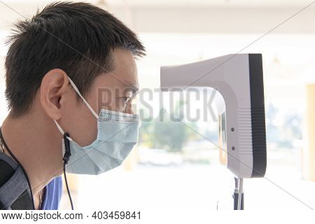 Man approached the forehead thermometer sensor to detect body heat,Temperature measurement points an