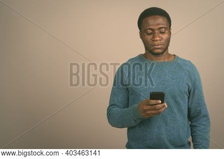 Young African Man Using Mobile Phone Against Gray Background In Black And White