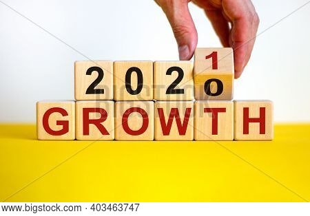 Symbol Of 2021 Growth. Businessman Turns A Wooden Cube And Changes Words 'growth 2020' To 'growth 20