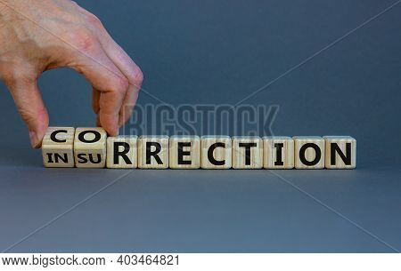 Correction Vs Insurrection Symbol. Businessman Turns Wooden Cubes And Changes Word 'insurrection' To