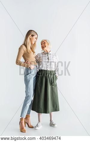 Full Length Of Cheerful Granddaughter And Senior Granny Standing With Hands In Pockets On White