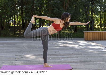 30th Slender Woman With A Beautiful Body Practices Yoga In The Park In The Morning. Healthy Lifestyl
