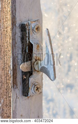An Old, Not Modern Latch On An Open Wooden Door. The Lock Is Covered With Paint, The Latch Is On The