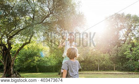 Young Mother Playing With Her Toddler Son Blowing Soap Bubbles For Him To Catch Outside In Beautiful