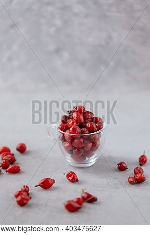 Glass Cup Of Dog Rose On A Grey Stone Background