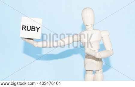 Business And Design Concept - Wooden Mannequin With Surreal Wood Cube Ruby. The Symbol Of Leadership