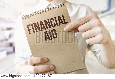 Text Financial Aid On Brown Paper Notepad In Businessman Hands In Office. Business Concept