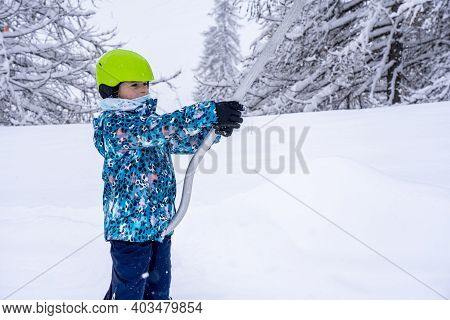 Blurred Focus Background. A Girl Lifting On The Ski Drag Lift Rope In Blue Sport Outfit On The Ski R