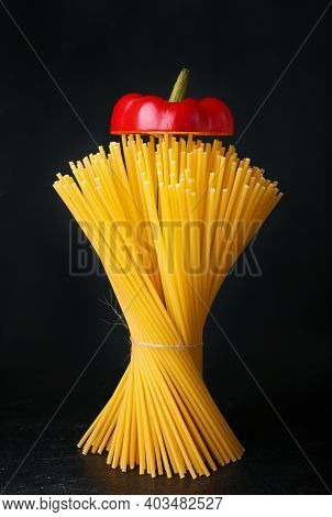 Raw Spaghetti On Dark Background. Uncooked Pasta With Copy Space. A Bunch Of Spaghetti Stands On A B