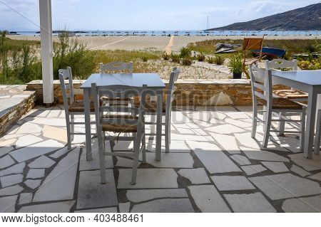 Ios, Greece - September 21, 2020: Tables And Chairs In Greek Restaurant At Manganari Beach On Ios Is