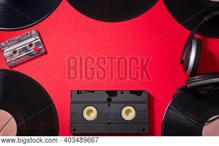 Retro Vintage Music Vintage Vinyl Disks, Audio Cassette, Video Cassette On Red Background. Copy Spac