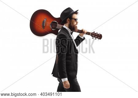 Musician walking with an acoustic guitar on his shoulder isolated on white background