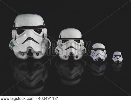 JAN 13 2021: various sized Star Wars Imperial Stormtrooper helmets - family concept - buckets - Hasbro action figures
