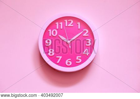 Pink clock on pink painted wall. Minimal time concept. Chrismas eve or new year idea. Stylish analog clock hanging on wall, space for text