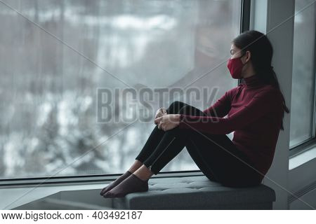 Winter depression because of coronavirus confinement. Sad Asian woman alone during city lockdown wearing face mask indoors at home covid. Anxiety, stress, mental health issues.