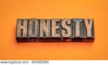 honesty word abstract in vintage letterpress wood type against orange handmade paper