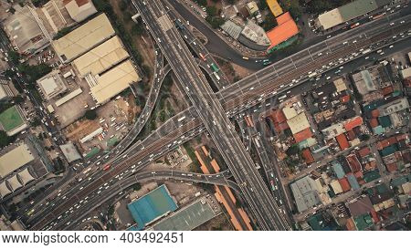 Top down of cross road traffic with cars, trucks, vehicles in aerial view. Downtown of Manila city with colorful buildings roofs at roadside. Philippines urban lifestyle with local journey