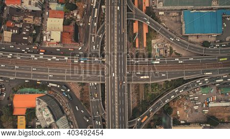 Top down of downtown traffic road at cityscape urban scenery in aerial view. Car park at high buildings, freeway with cars and trucks. Local transportation of Philippine capital Manila town drone shot