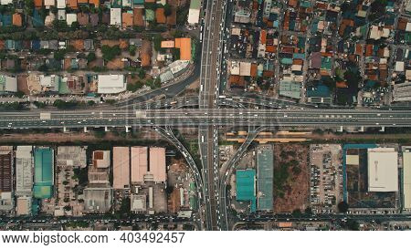 Top down cars drive at cross freeway in aerial view. Highway traffic transportation at Manila city on Luzon Island, Philippines, Asia. Wonderful cityscape of downtown centre