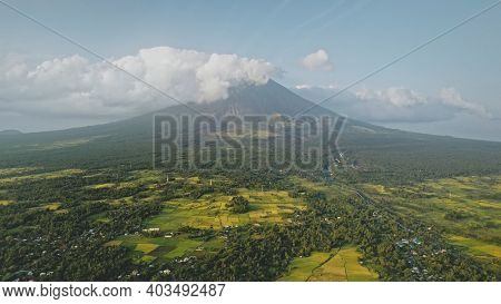 Volcano eruption at green tropical valley aerial. Mayon mount at amazing nobody nature landscape. Greenery meadow with tropic plants, grasses, trees. Cinematic mist haze drone shot