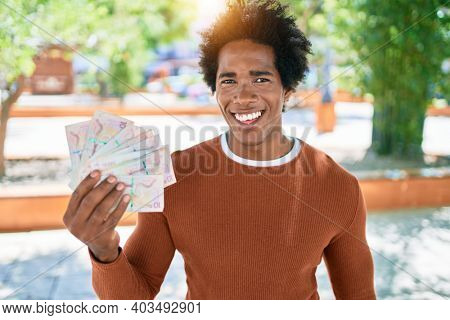 Young african american man smiling happy. Standing with smile on face holding colombian pesos banknotes at town street.