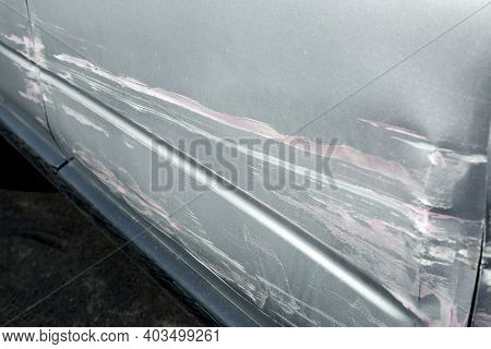 Car Damage After An Accident Crash, Scratched And Crumpled Driver's Door And Fender Closeup Spoiled