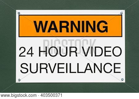 Warning 24 hour video surveillance sign on green metal background.